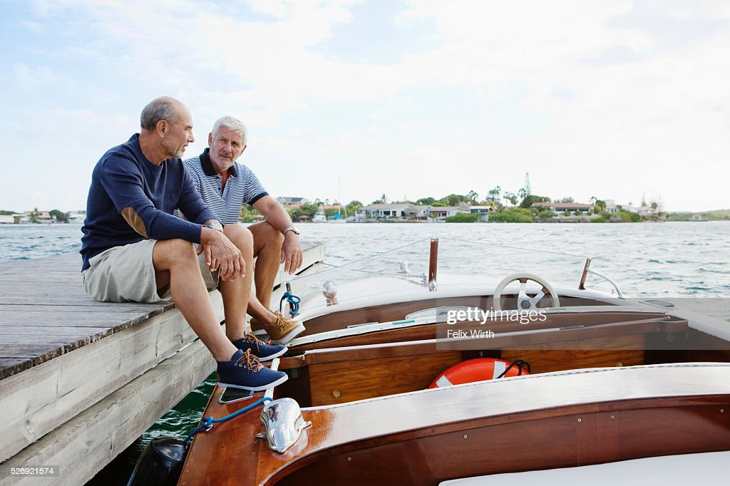 Two senior friends resting on jetty with moored motorboat : Foto de stock