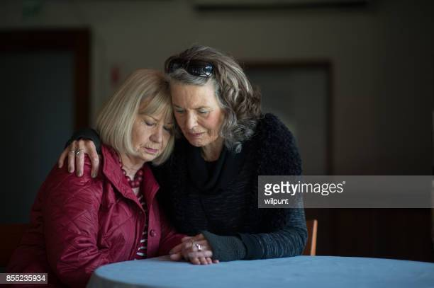 Two senior ladies supporting one another