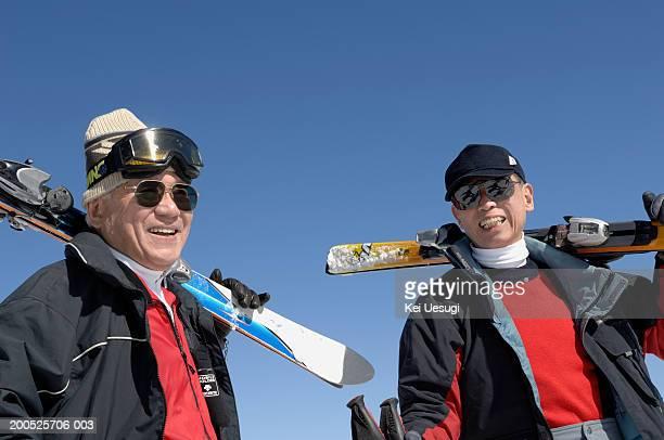 Two senior men carrying skis over shoulders, smiling