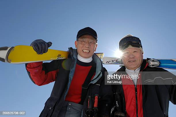 Two senior men carrying skis, portrait, low angle view