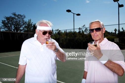 Two senior men drinking scotch on the tennis court : Stock Photo