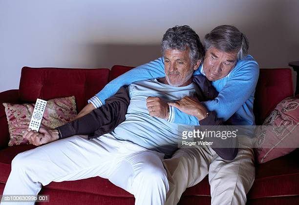 Two senior men fighting for remote control on sofa