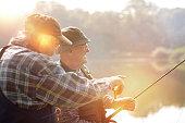 Two senior men fishing on lake
