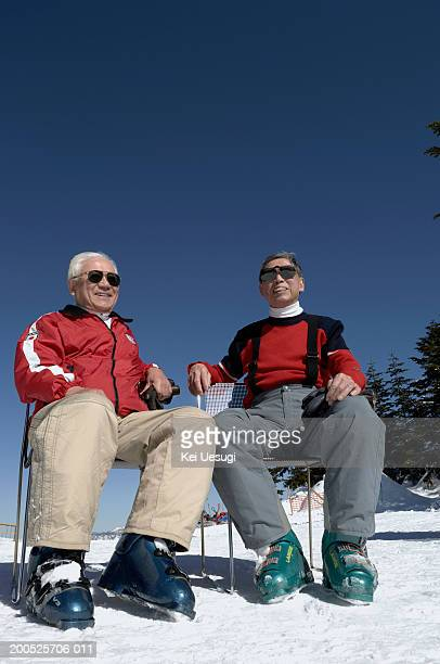 Two senior men in ski-wear sitting on chairs outdoors, low angle view