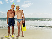 Two senior men on beach, snorkle masks on head, smiling, portrait