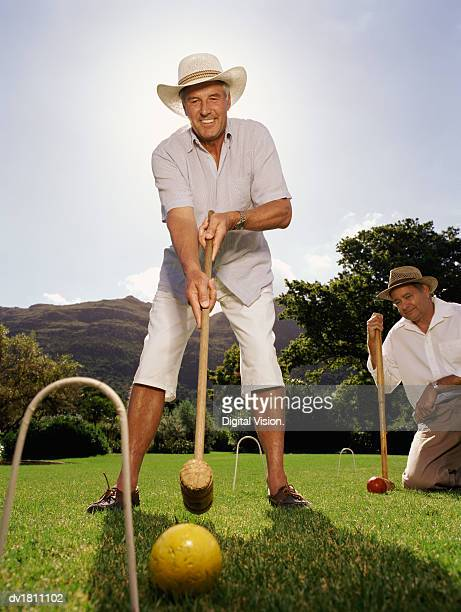 Two Senior Men Playing a Game of Croquet