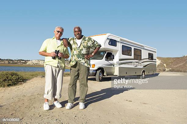 Two Senior Men Stand Side by Side By a River, in Front of a Parked Motor Home