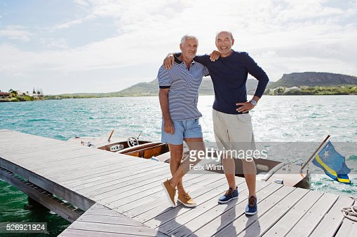 Two senior men standing on jetty : Stock Photo