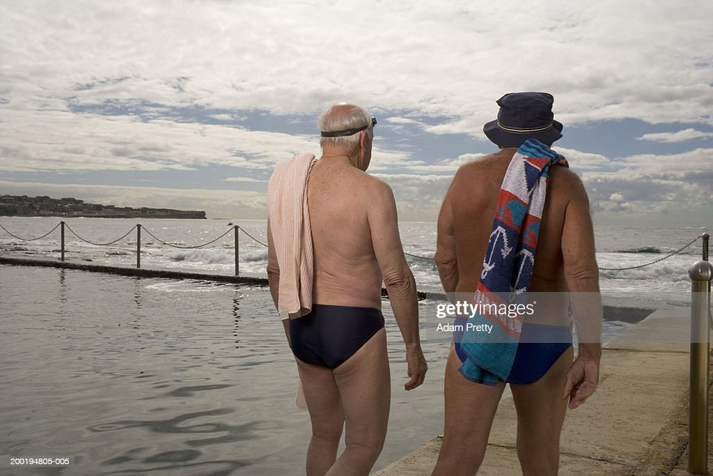 Two senior men walking at side of infinity pool, rear view : Stock Photo