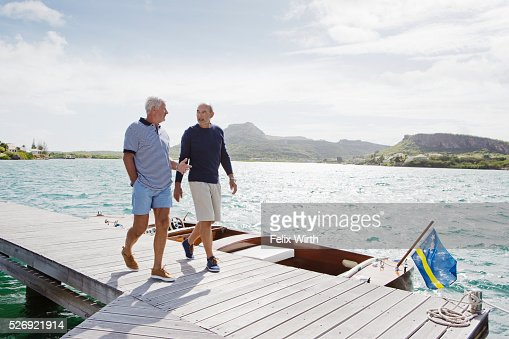 Two senior men walking on jetty : Stock Photo