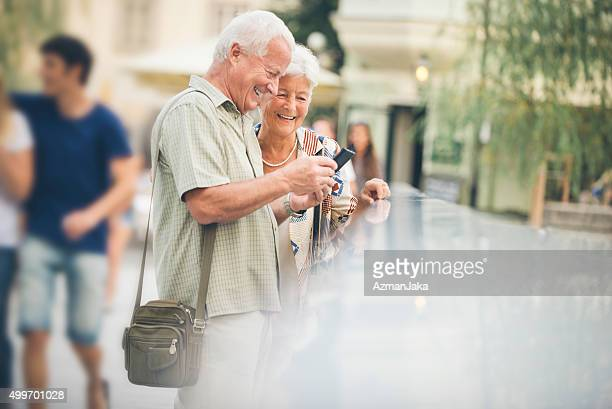 Two senior tourists looking at smart phone