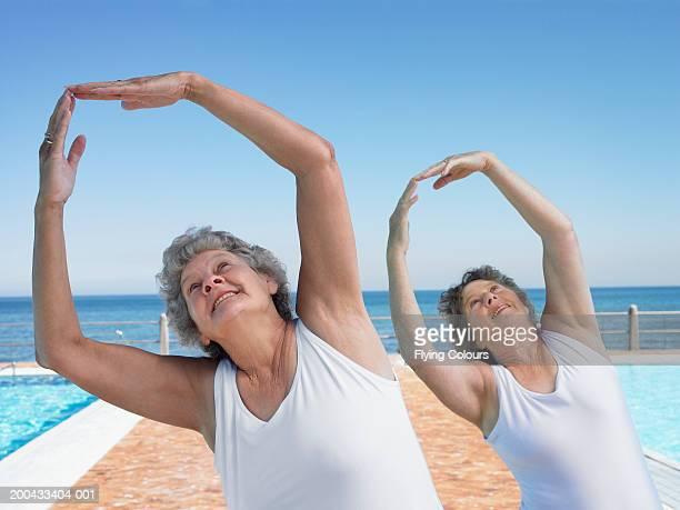Two senior women exercising by swimming pool, smiling