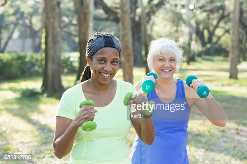 Two senior women exercising in park with hand weights : Stock Photo