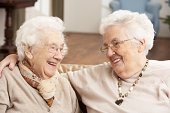 Two Senior Women Friends At Day Care Centre Sitting On Sofa Smiling At Each Other
