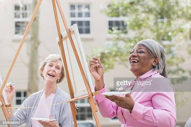 Zwei alte Frauen Spaß haben Malerei in der Kunst-Klasse