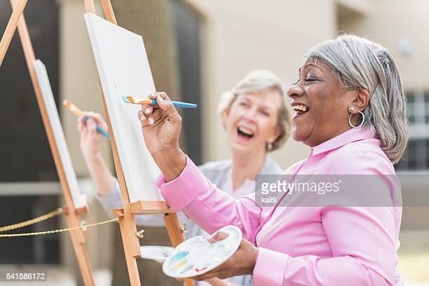 Two senior women having fun painting in art class