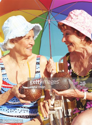 Two senior women holding coconuts, smiling at each other, close-up : Stock Photo