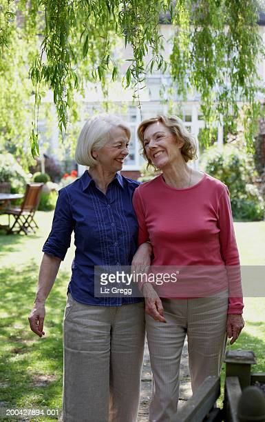Two senior women in garden linking arms, smiling