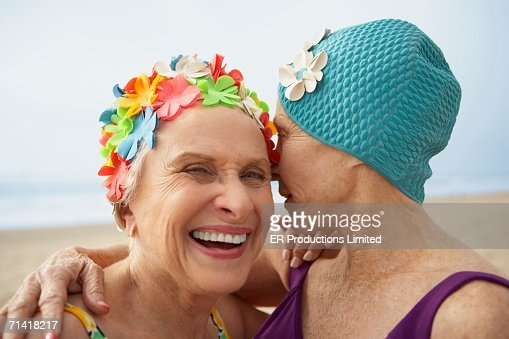 Two senior women in swim caps at the beach