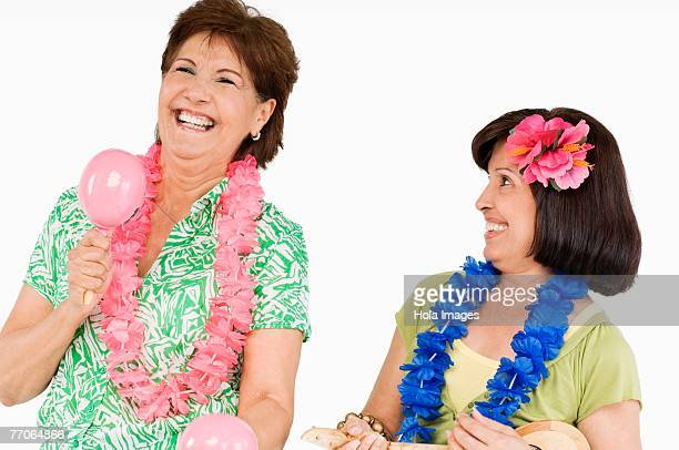 Two senior women playing ukulele and maracas