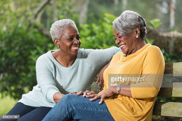 Two senior women sitting on park bench laughing