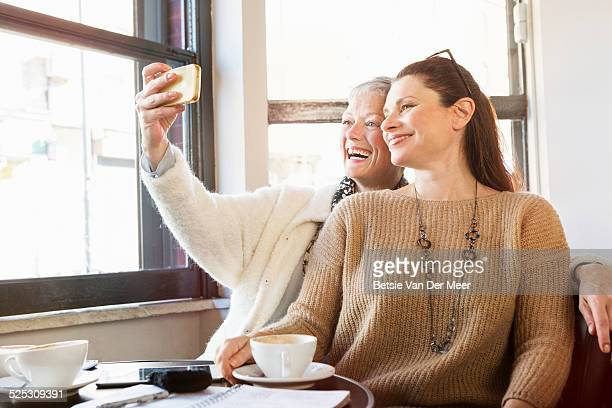 Two senior women taking selfie in cafe.