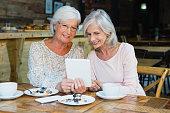 Two senior women using digital tablet in cafe