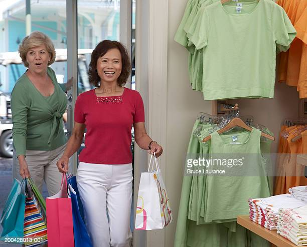 Two senior women walking into a store holding shopping bags, smiling