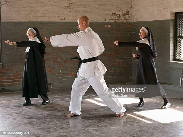 Two senior women with man practicing karate