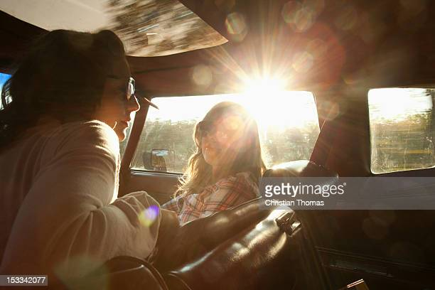 Two serene rockabilly women in the front seat of a vintage car