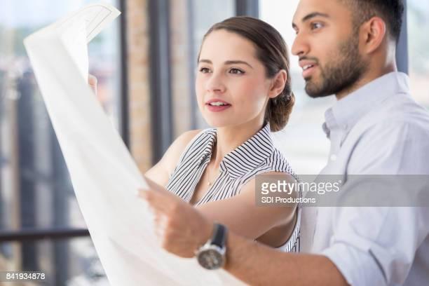 Dos compañeros de trabajo arquitectónicos serio estudian plano