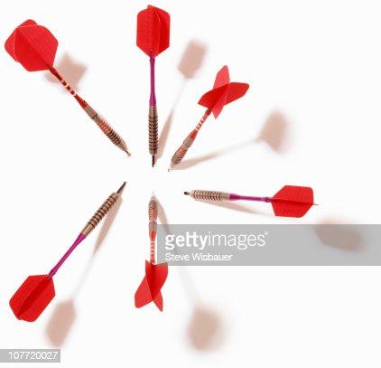 Two sets of darts with red flights stuck in wall