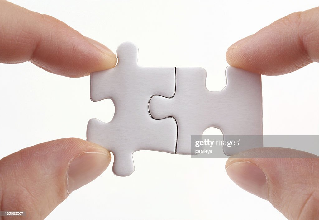 Two sets of fingers holding two puzzle pieces together : Stock Photo