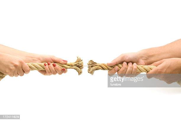 Two sets of hands playing tug-of-war with a frayed rope