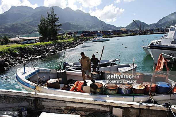 Two Seychellois coast guard marines walk on November 28 2009 over two outboard motor large skiffs that were used by Somali pirates and consequently...