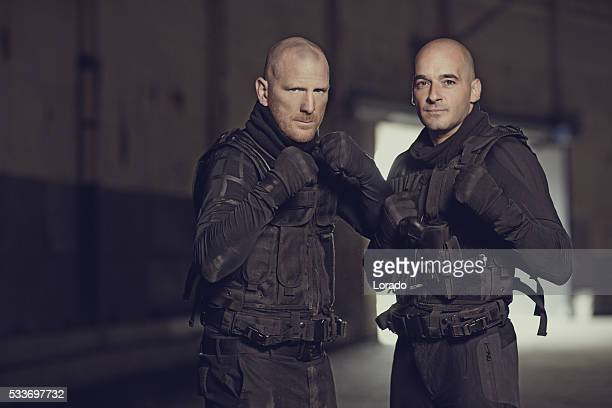 Two shaven headed swat team members posing in abandoned warehouse