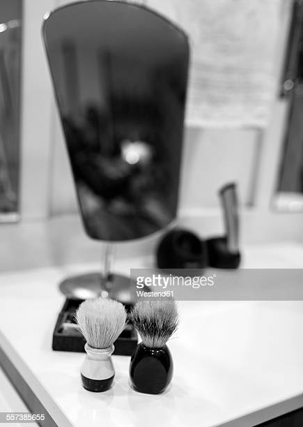 Two shaving brushes and a mirror in a barbershop