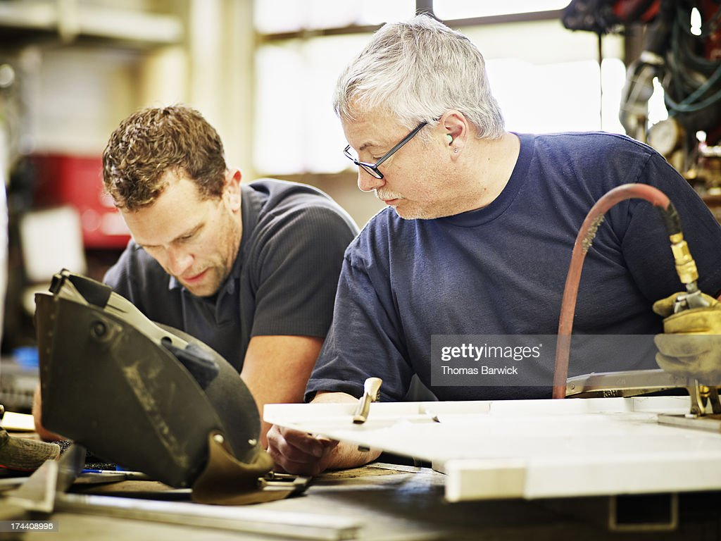 Two sheet metal workers discussing project