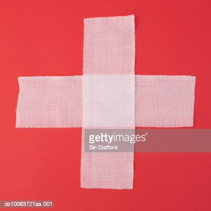 Two sheets of gauze forming cross on red background, overhead view : Stock Photo