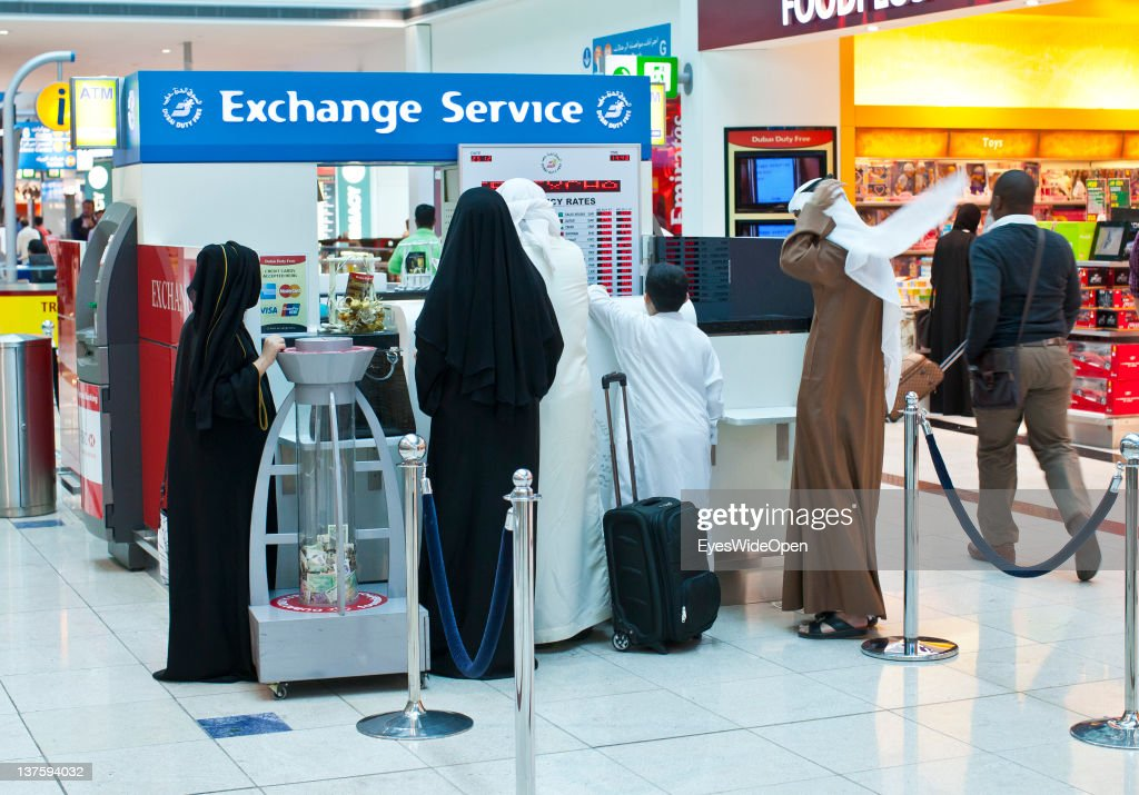 Two sheikhs with luggage and women in burkas want to change money at an exchange service at Dubai Airport on December 25, 2011 in Dubai, United Arab Emirates