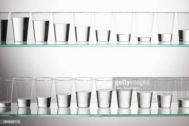 Two shelves with glasses of water filled with varying amounts of water
