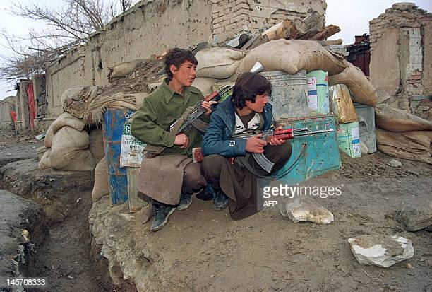 Two Shiite teenagers of the minority HezbiWahdat faction armed with Kalashnikovs peer around their bunker during a exchange of smallarms fire with...