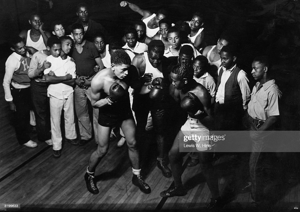 Two shirtless African-American teenagers spar in a boxing match as a crowd of others looks on in the New Haven Boys Club, Connecticut.