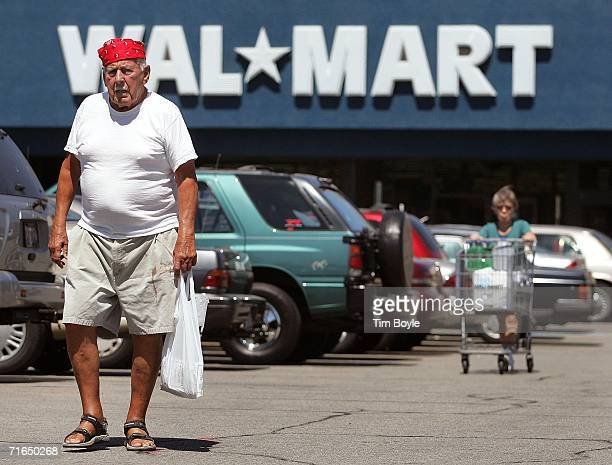 Two shoppers walk in the parking lot outside a WalMart store August 15 2006 in Mount Prospect Illinois WalMart profits fell 26 percent for the...