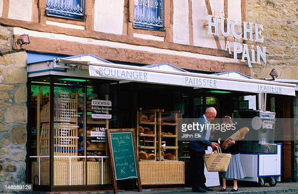 Two shoppers with a rather large loaf of bread, standing outside a boulangerie, or if you prefer, a bakery