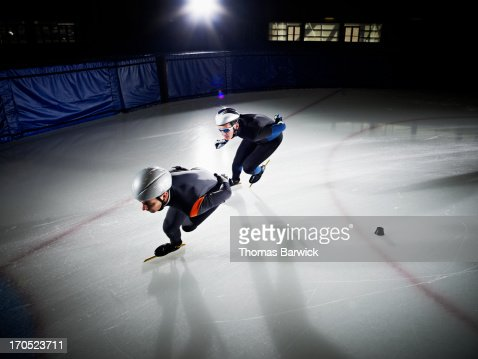 Two short track speed skaters racing : Stock Photo