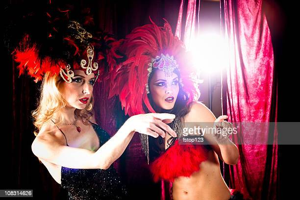 Two showgirls on stage, pointing to right