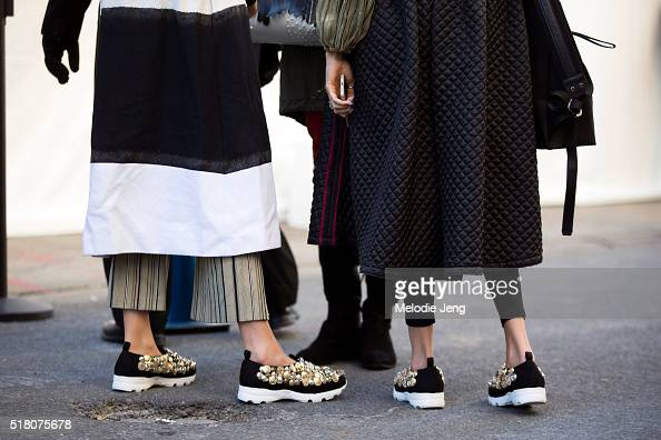 Two showgoers wears matching embellished lowrise sneakers at the Zimmerman show during New York Fashion Week Women's Fall/Winter 2016 on February 12...