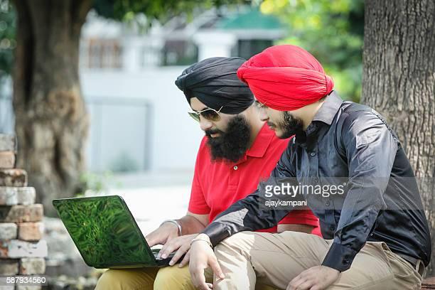 Two Sikh men using laptop