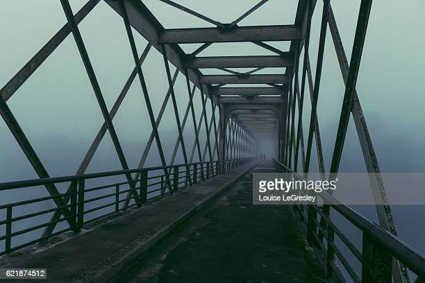 Two silhouettes crossing an old steel footbridge on a foggy morning